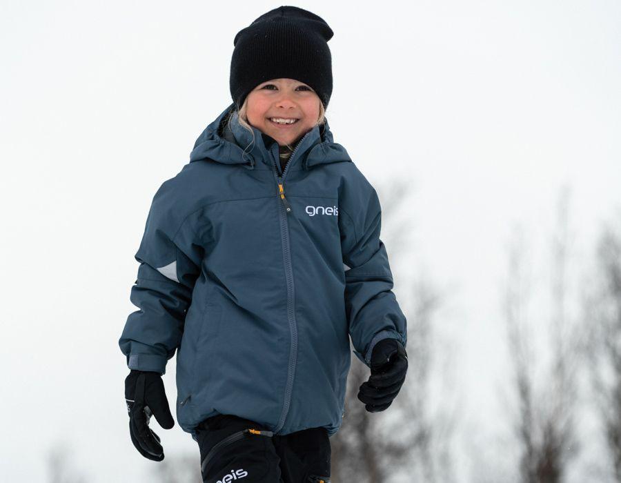Glad flicka i Gneis vinterkläder för barn