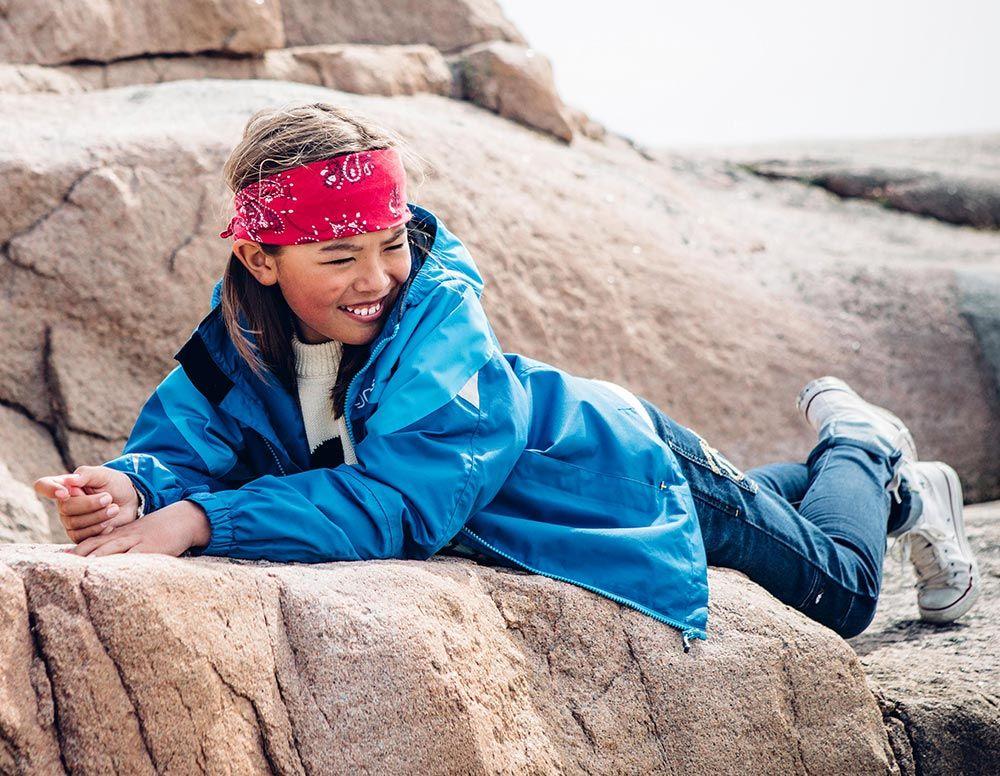 Barn i blå skaljacka ligger på sten