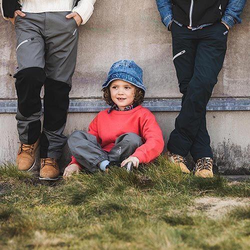 Barn i byxor i gräset