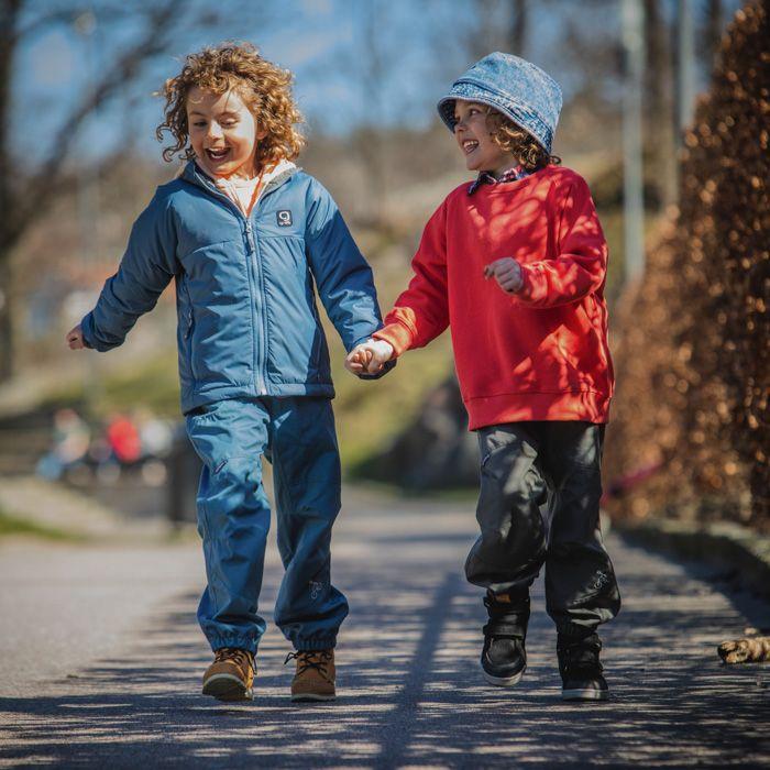 Lekande barn i Gneis friluftsbyxor