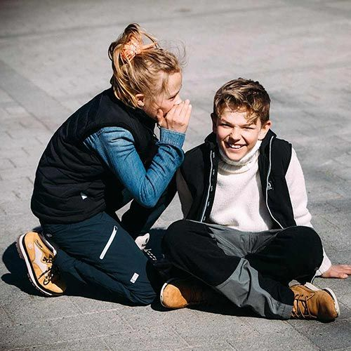 Barn i friluftskläder viskar