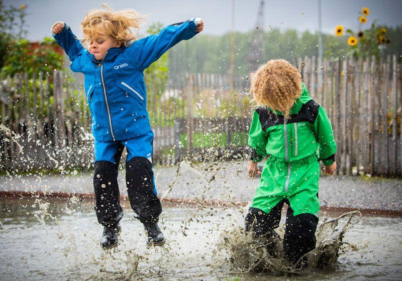 Barn hoppar i vattenpölar med Gneis skalkläder