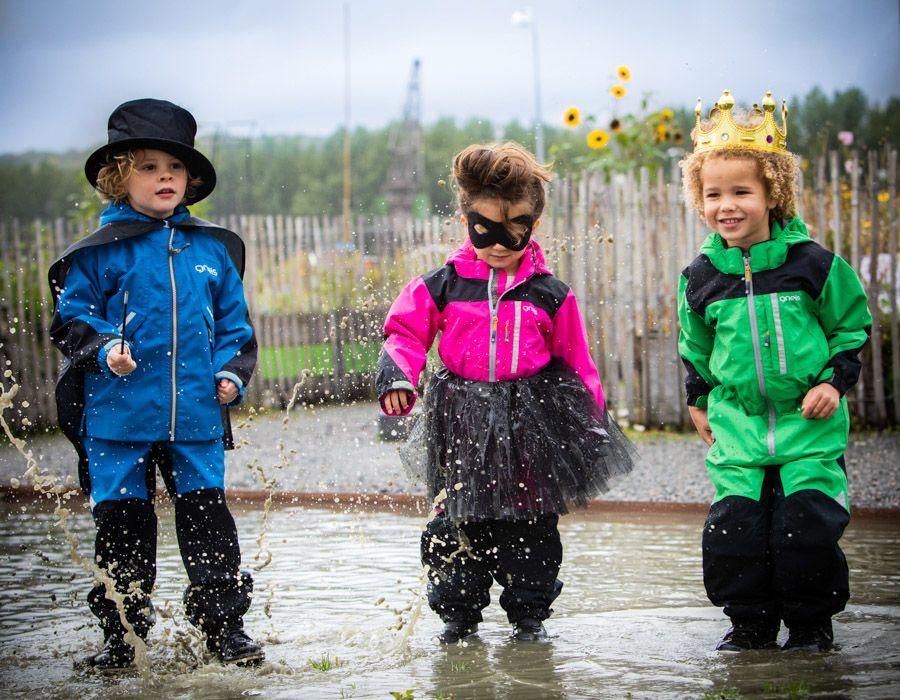 Barn Gneis skalkläder som hoppar i pöl
