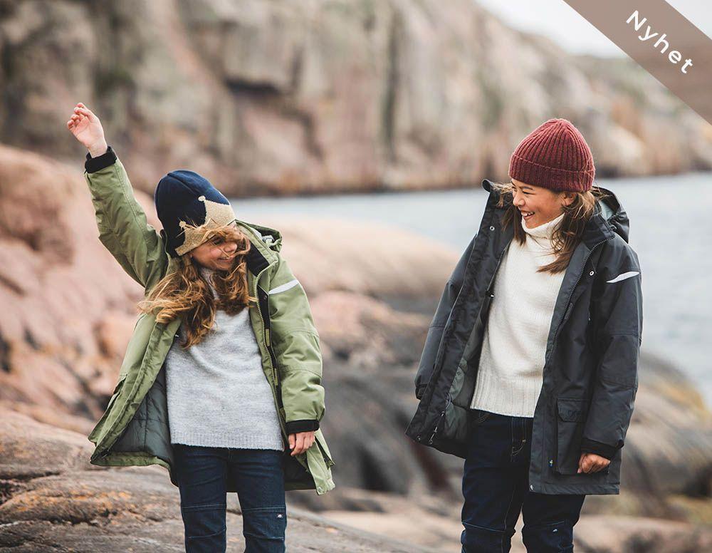 Barn i vinterparkas står på klippor
